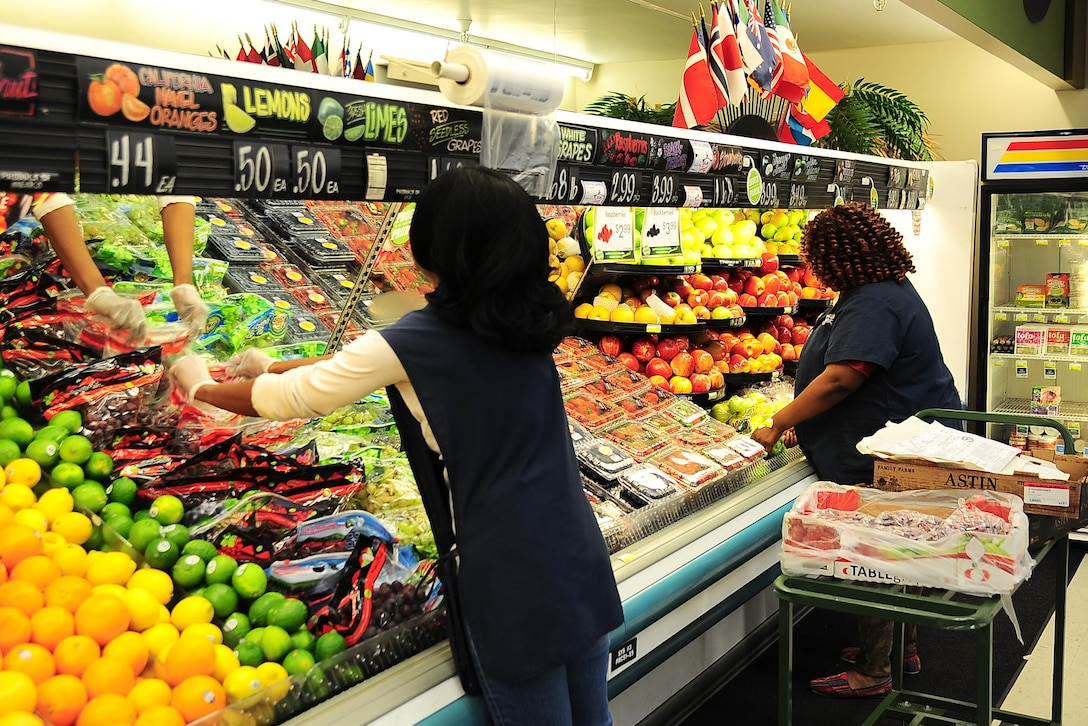 Quintina Walters, Store Associate, and Valandria James, Store Worker, stock produce March 1, 2017, at Columbus Air Force Base, Mississippi. Upcoming changes include replacing all refrigeration on the sales floor to include deli, produce and meat department cases. (U.S. Air Force photo by Senior Airman Kaleb Snay)