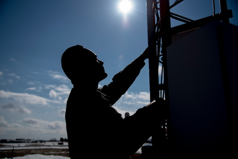 U.S. Air Force Airman 1st Class Christopher Blackwell, a 35th Operations Support Squadron airfield systems technician, climbs an AN/FMQ 19 at Misawa Air Base, Japan, Feb. 27, 2017. The AN/FMQ 19 is an integrated system of weather sensors that measure, collect and disseminate meteorological data to help pilots, weather personnel and air traffic controllers prepare and monitor weather forecasts. By Airfield systems Airmen enable, F-16 Fighting Falcons to contribute to Pacific Air Forces' mission to deter aggression with allies and maintain peace and stability in the Indo-Asia- Pacific region. (U.S. Air Force photo by Airman 1st Class Sadie Colbert)
