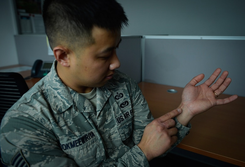 Staff Sgt. Srun Sookmeewiriya, 313th Expeditionary Operations Support Squadron NCO in charge of reports, points to scarring on his left wrist on Ramstein Air Base, Germany, Feb. 16, 2017. Sookmeewiriya attempted to commit suicide twice at a young age. He now shares his story occasionally to the public, encouraging struggling Airmen to seek help and be resilient.