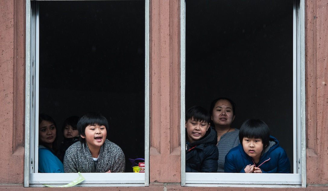 A family peer out their house windows at a parade during fasching, a festival held across Europe, in the city of Ramstein, Germany, Feb. 28, 2017. During modern fasching, people parade around cities to welcome the new season while saying goodbye to winter. (U.S. Air Force photo by Senior Airman Lane T. Plummer)