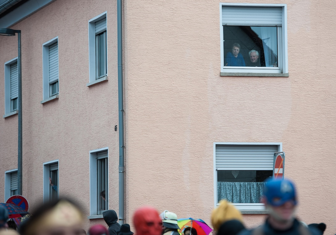 An elderly couple stare out their window to view the parade below them during fasching, a festival held across Europe, in the city of Ramstein, Germany, Feb. 28, 2017. Fasching is a time of festivity and merry making—a time where common place people take a chance to free themselves for personal expression and celebration. (U.S. Air Force photo by Senior Airman Lane T. Plummer)