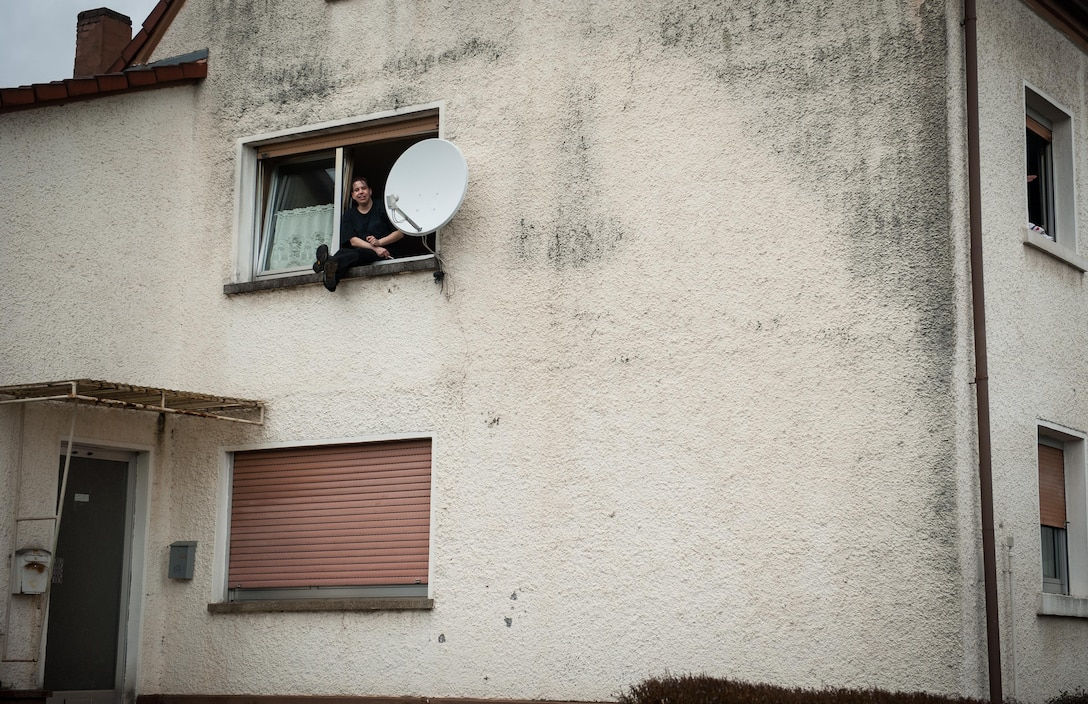 A man sits on his windowsill to observe the parades outside his apartment during fasching, a festival held across Europe, in the city of Ramstein, Germany, Feb. 28, 2017. These festivals are associated with festivals of the Christian church, however, they go further back to Pagan times, and was a way of driving out the evil spirits of winter and encouraging the coming of spring and good crops. (U.S. Air Force photo by Senior Airman Lane T. Plummer)