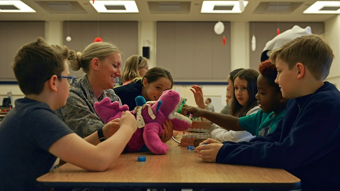 Maj Rachel Weber, 31st Dental Squadron Periodontist, educates children on proper brushing and flossing techniques, Feb. 15, 2017, at Aviano Air Base, Italy. Airmen from the 31st DS visited the elementary school, child development centers and library for Children's Dental Health Month. (U.S. Air Force photo by Senior Airman Cary Smith)