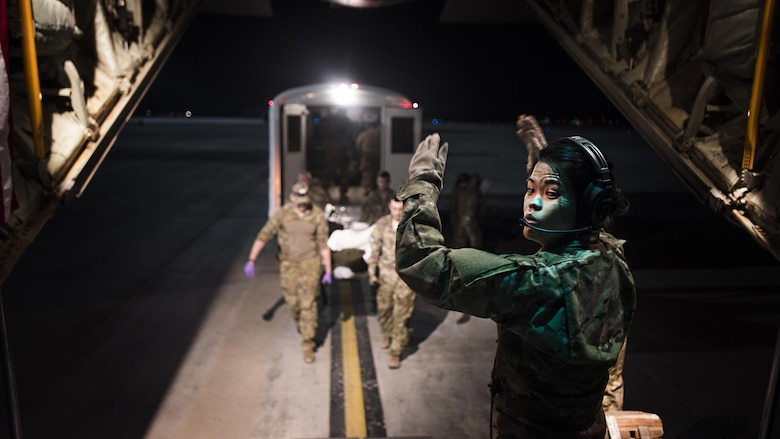 1st Lt. Sarah Jun, 455th Aeromedical Evacuation Squadron flight nurse, directs litter carriers bringing a patient onboard a C-130J Hercules to transport him from Kandahar Regional Military Hospital, Kandahar Airfield, to the Craig Joint Theater Hospital, Bragram Airfield, Afghanistan Feb. 22, 2017. The 455th EAES creates and operates a portable intensive care unit aboard aircraft that enables them to transport critically injured or ill patients to a higher level of care. (U.S. Air Force photo by Staff Sgt. Katherine Spessa)