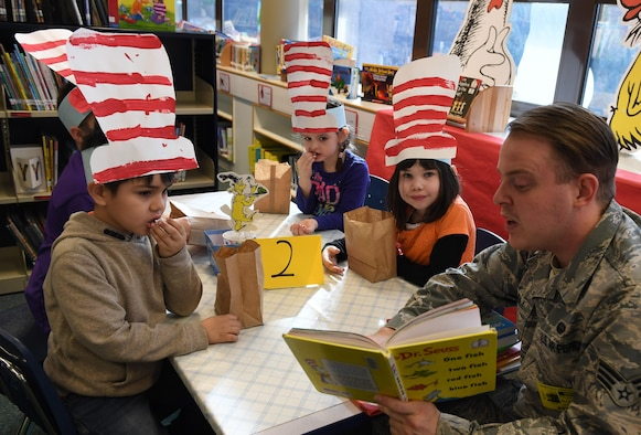 Senior Airman Tyler Allen, U.S. Air Forces Europe Warrior Prep Center systems administrator, reads to elementary school students during the Seuss Reading Café at Ramstein Air Base, Germany, March 3, 2017. More than 50 service members volunteered to read to students during the week-long event. (U.S. Air Force photo by Staff Sgt. Nesha Humes)