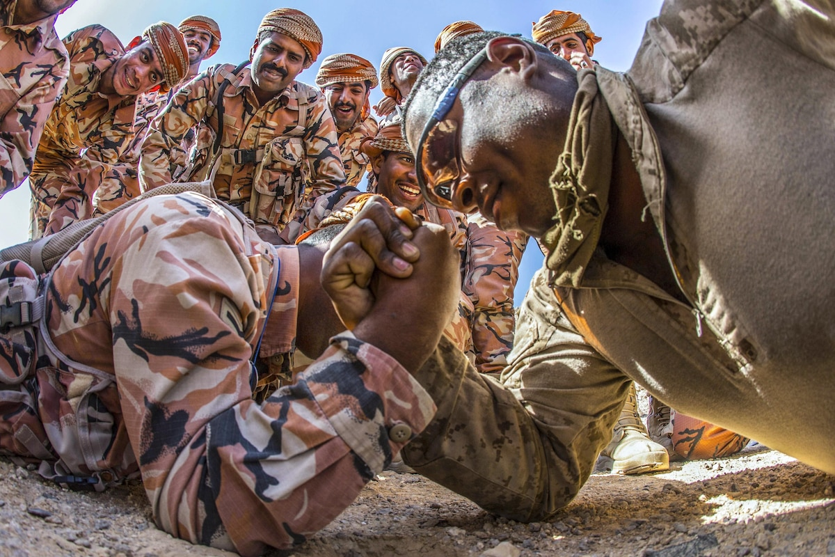 A Marine arm wrestles an Omani soldier on the ground.