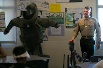 Staff Sgt. Robert Bouchard,  explosive ordnance disposal technician, answers Painted Hills Middle School students question during a career day in Desert Hot Springs, Calif., Feb. 23, 2017. The purpose of the visit was to further the installations commitment to the community and help inspire children to begin thinking about their future.  (Official Marine Corps Photo by Cpl. Julio McGraw/Released)