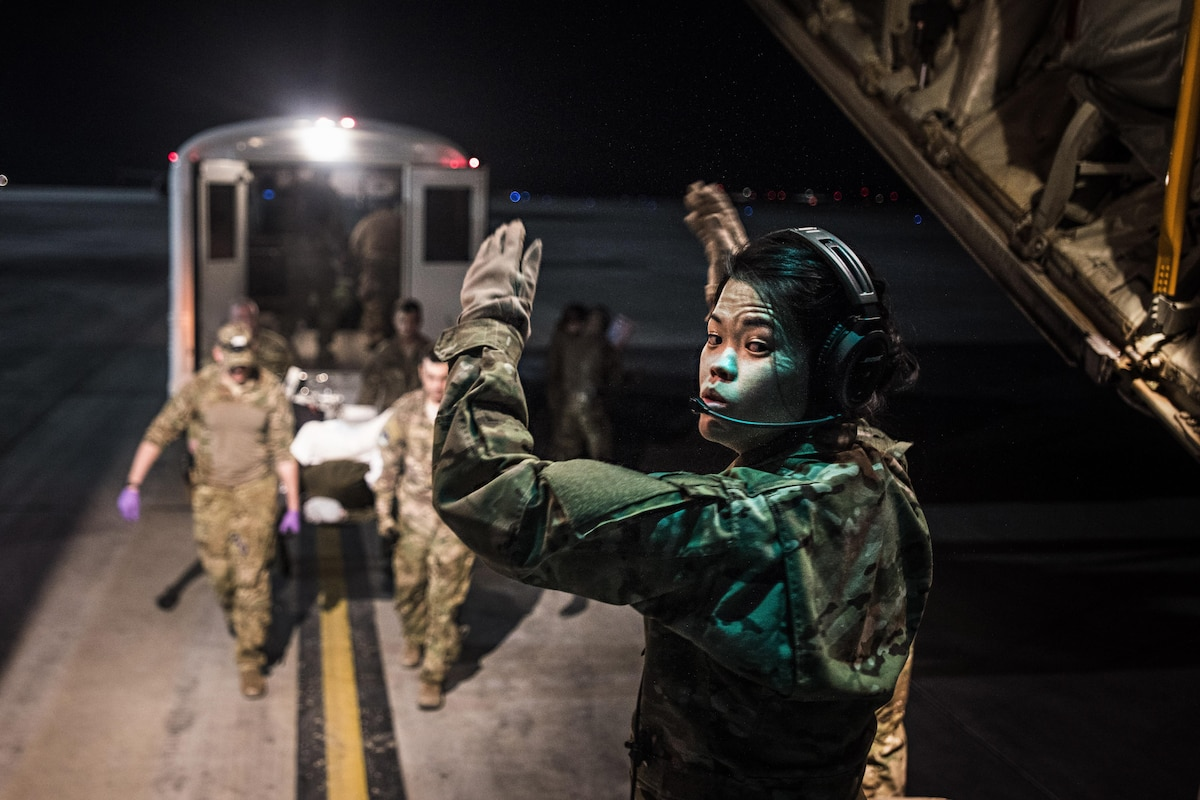 An airman directs troops bringing a patient onto a C-130J Hercules for transport.