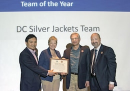 From left, Phetmano Phannavong, DC Department of Energy and Environment, DC floodplain manager; Stacey Underwood, U.S. Army Corps of Engineers, Baltimore District, Silver Jackets Program coordinator; and Mark Baker, National Park Service, Dam and Levee Safety officer, are recognized as part of the District of Columbia Silver Jackets Team as state Silver Jackets team of the year, during the 2017 Interagency Flood Risk Management Workshop in St. Louis, March 2, 2017. Mark Roupas (at right), Corps, Office of Homeland Security deputy chief, presented the team members with the award during the workshop. The Corps Baltimore District, NPS and DOEE jointly lead the DC Silver Jackets, which is an interagency team that manages flood risks in the District. There are active Silver Jackets teams in 47 states, plus the District, and the program is sponsored by the Corps. (Courtesy photo)