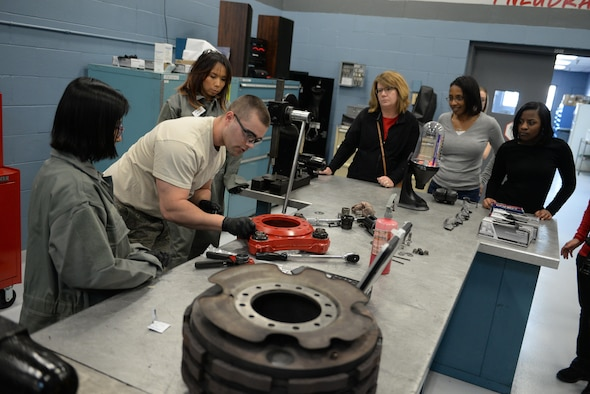 Airman 1st Class Kameron Hamilton, a 55th Maintenance Squadron hydraulics system journeyman, shows 55th MXS spouses how to work on a RC-135 break assembly part in the Bennie L. Davis Maintenance Facility at Offutt Air Force Base, Neb., Feb. 17, 2017. The tour was designed to show spouses what their significant others do to support the Air Force mission.(U.S. Air Force photo by Zachary Hada)