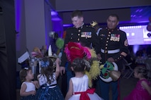 Marines are offered hats by their daughters during the annual Father Daughter Dance at building 1707 aboard Marine Corps Air Ground Combat Center, Twentynine Palms, Calif., Feb. 25, 2017. Marine Corps Community Services hosted the event to provide an opportunity for Marines and sailors to spend time with their daughters. (U.S. Marine Corps photo by Cpl. Medina Ayala-Lo)