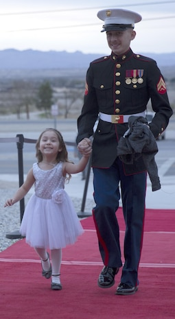 Cpl. Justin Falcon, automotive organizational mechanic, 7th Marine Regiment, escorts his daughter, Madelyn, 4, into the reception hall of the annual Father Daughter Dance at building 1707 aboard Marine Corps Air Ground Combat Center, Twentynine Palms, Calif., Feb. 25, 2017. Marine Corps Community Services hosted the event to provide an opportunity for Marines and sailors to spend time with their daughters. (U.S. Marine Corps photo by Cpl. Medina Ayala-Lo)