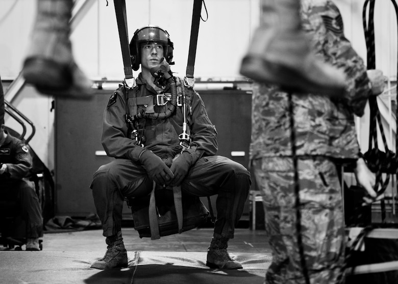 A member of the 23rd Bomb Squadron hangs in a simulated parachute harness at Minot Air Force Base, N.D., Feb. 22, 2017. Egress and emergency parachute training teaches personnel how to safely exit the aircraft and return to the ground after an emergency. (U.S. Air Force photo/Senior Airman J.T. Armstrong)