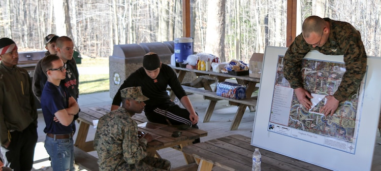 U.S. Marine Gunnery Sergeant Paul Folk teaches his poolees the proper way to use a protractor during a class on land navigation at Hogback Ridge Park February 18. The class was designed to educate the poolees on the basics of land navigation to better prepare them for recruit training at Marine Corps Recruit Depot Parris Island, South Carolina. Land navigation is taught during recruit training and is an important military skillset. (U.S. Marine Corps photo by Sgt. Stephen D. Himes/Released)