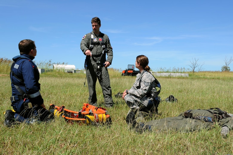 Rescue Crewman Kurt Pride, Royal Australian Air Force Base Tindal helicopter unit member, U.S. Air Force Capt. Paul Ward, 90th Fighter Squadron Flight Doctor, and Tech. Sgt. Layla Dispense, 90th FS Independent Duty Medical Technician, prepare a dummy for transport on a stretcher during helicopter rescue training at RAAF Base Tindal, Feb. 28, 2017. Ward and Dispense are deployed to Australia as part of the Enhanced Air Cooperation, a joint training and exercise initiative under the Force Posture Agreement between the U.S. and Australian governments. (U.S. Air Force photo by Staff Sgt. Alexander Martinez)