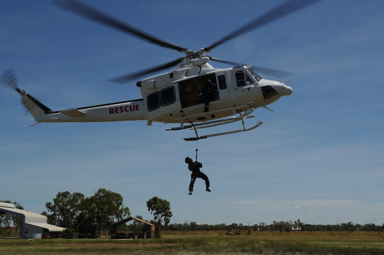 U.S. Air Force Capt. Paul Ward, 90th Fighter Squadron Flight Doctor, is raised to a helicopter by a winch during helicopter rescue training at RAAF Base Tindal, Feb. 28, 2017. Ward is deployed to Australia as part of the Enhanced Air Cooperation, a joint training and exercise initiative under the Force Posture Agreement between the U.S. and Australian governments. (U.S. Air Force photo by Staff Sgt. Alexander Martinez)