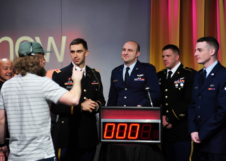 """U.S. Army Soldiers and U.S. Air Force Airmen from Joint Base Lewis-McChord, Wash., listen as a King 5 """"New Day"""" show camera operator explains rules of play prior to kicking off a round of on-air trivia, Feb. 28, 2017 in Seattle, Wash. During the game, servicemembers competed against a group of four civilians, and ultimately walked away with a win under their belts. (U.S. Air Force photo/Staff Sgt. Whitney Amstutz)"""