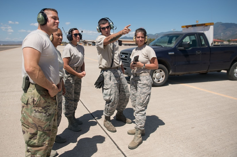 "Staff Sgt. Sean Sullivan, 612th Air Base Squadron crew chief, shows participants of a ""Crew Chief For a Day"" program where an incoming heavy aircraft will be taxiing. The program aims to get other servicemembers from JTF-Bravo to come out to the airfield and experience a day in the life of a U.S. Air Force crew chief."