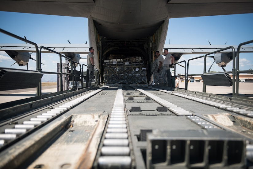"""Participants of the 612th Air Base Squadron's """"Crew Chief for a Day"""" program watch how cargo is loaded into a C-130 Hercules aircraft at Soto Cano Air Base, March 2. The program aims to get other servicemembers from JTF-Bravo to come out to the airfield and experience a day in the life of a U.S. Air Force crew chief."""