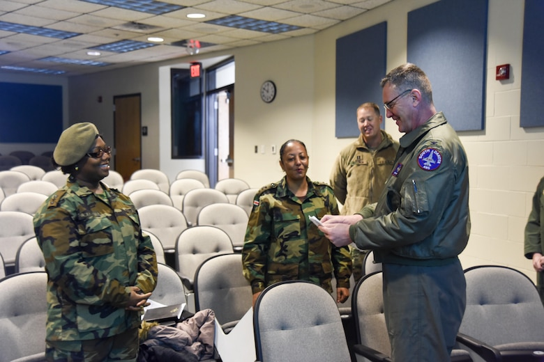 Col. Nate Alholinna, 114th Fighter Wing commander, speaks with Capt. Eria Wamenie, Suriname Army, Head of S4, and Capt. Sandra Ponit, Suriname Army, Deputy S2, Military Police, about the mission of the 114th Fighter Wing March 3, 2017 at Joe Foss Field, S.D. Female Officers of the Suriname Army visited with members of the South Dakota Air National Guard as part of a Women in Leadership Subject Matter Exchange program. (U.S. Air National Guard photo by Staff Sgt. Duane Duimstra/Released)