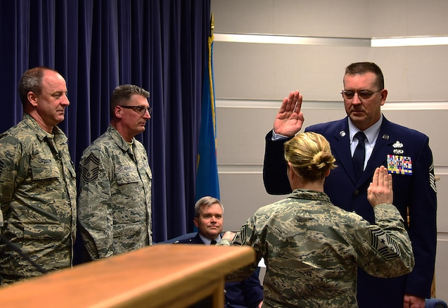 SMSgt. John Young, Supply Chief, 166th LRS, takes the chief's oath from Command CMSgt. Shaune Peters, 166th Airlift Wing, during his promotion ceremony to Chief Master Sergeant, Delaware Air National Guard, New Castle, De., March 3, 2017. (U.S. Air National Guard photo by SSgt. Andrew Horgan/released)