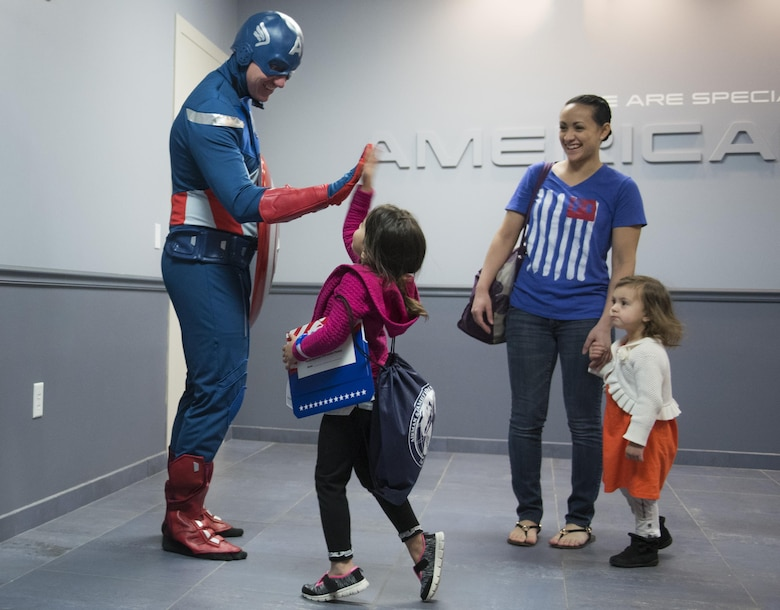 """A new 919th Special Operations Wing deployer high-fives Captain America before moving out during the Operation Hero event at Duke Field, Fla., March 4.  The wing held a mock deployment for the Reserve children to include a deployment line, simulated flight and a """"down range"""" location with games and displays.  (U.S. Air Force photo/Samuel King Jr.)"""
