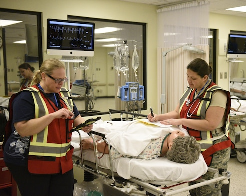 Maj. Cari Matthews, a physician with the Montana Air National Guard, evaluates a patient while Kristi Thompson, a nurse from the Great Falls Clinic, completes a chart Feb. 16, 2017, during a mass casualty exercise at the Noble Training Center at the Federal Emergency Management Agency's Center for Domestic Preparedness in Anniston, Alabama. The emergency department staff was challenged with overwhelming numbers of patients following a simulated terrorist attack.  (US Air National Guard photo/Staff Sgt. Lindsey Soulsby)