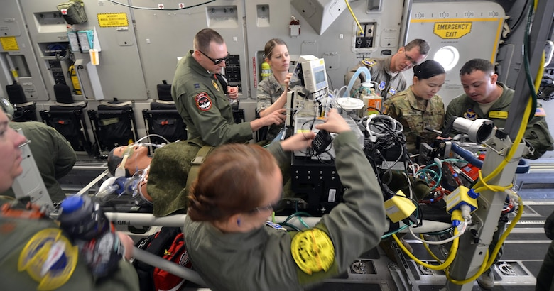 Air Force and Army medics stabilize a simulated patient connected to an extracorporeal membrane oxygenation machine (ECMO) upon boarding a C-17 Globemaster III for transport from Patrick Air Force Base, Florida, March 4, 2017 as part of the 5th annual MEDBEACH joint medical response exercise. ECMO is a treatment that uses a pump to circulate blood through an artificial lung back into the bloodstream of a patient. (U.S. Air Force photo/Tech. Sgt. Lindsey Maurice)