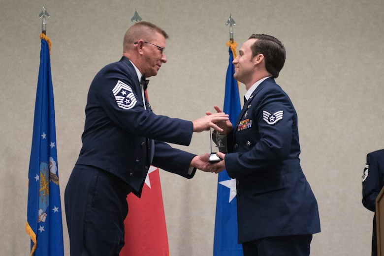 Staff Sgt. Daniel Keller, a combat controller for the 123rd Special Tactics Squadron, receives the Kentucky Enlisted Exceptional Performance Award from Chief Master Sgt. Jeff Moore, Kentucky's state command chief, during the Soldier and Airman of the Year banquet at the Kentucky Fair and Exposition Center, Louisville, Ky. on March 4, 2017. The winners were selected for their leadership and performance in their primary duties, dedication to self-improvement, and base and community involvement. (U.S. Air National Guard photo by Staff Sgt. Joshua Horton)