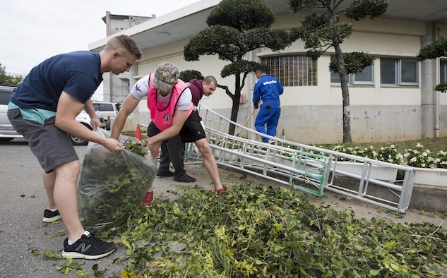 Airmen from the 909th Aircraft Maintenance Unit dispose of leaves during a volunteer event at Yara Elementary School March 5, 2017, at Kadena Town, Japan. Airmen from the 909th AMU volunteer in Kadena Town to better their selves and build community relations with local Okinawans. (U.S. Air Force photo by Senior Airman Omari Bernard/Released)