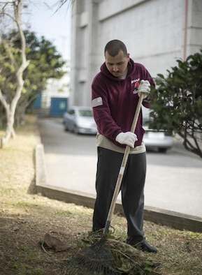 U.S. Air Force Airman Ryan Crean, 909th Aircraft Maintenance Unit aerospace propulsion apprentice, rakes leaves during a volunteer event at Yara Elementary School March 5, 2017, at Kadena Town, Japan. Airmen from the 909th AMU volunteer often in Kadena Town to be a part of the local community. (U.S. Air Force photo by Senior Airman Omari Bernard/Released)