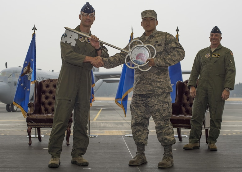 Maj. Gen. Mark Dillon, Pacific Air Forces vice commander, hands a ceremonial key to Staff Sgt. Gene Phonthipsavath, 374th Aircraft Maintenance Squadron dedicated crew chief, during a C-130J Super Hercules arrival ceremony at Yokota Air Base, Japan, March 6, 2016. Compared to older C-130s, the J model climbs faster and higher, flies farther at a higher cruise speed, and takes off and lands in a shorter distance. (U.S. Air Force photo by Staff Sgt. David Owsianka)