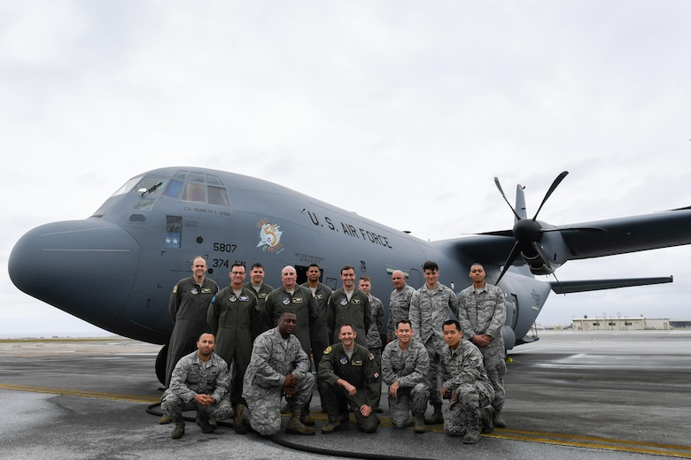 Members of the C-130J delivery team pose for a photo in front of a C-130J Super Hercules at Kadena Air Base, Japan, March 6, 2017. This is the first C-130J to be assigned to Pacific Air Forces.  Yokota serves as the primary Western Pacific airlift hub for U.S. Air Force peacetime and contingency operations. Missions include tactical air land, airdrop, aeromedical evacuation, special operations and distinguished visitor airlift. (U.S. Air Force photo by Staff Sgt. Michael Smith)