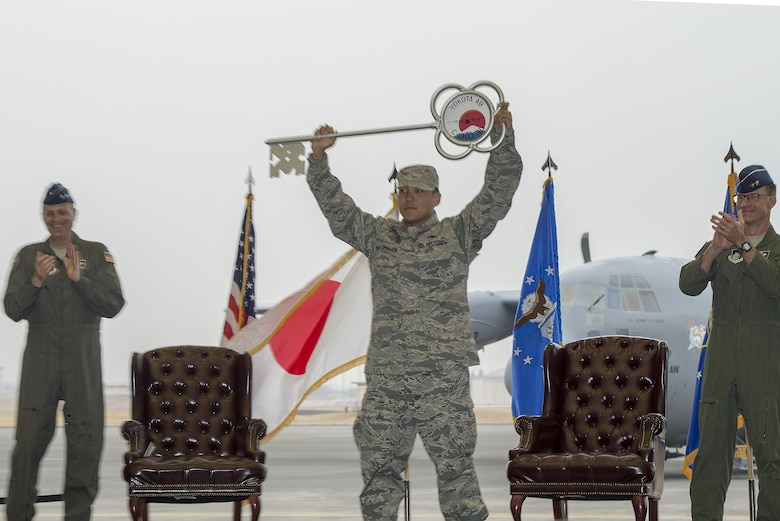 Staff Sgt. Gene Phonthipsavath, 374th Aircraft Maintenance Squadron dedicated crew chief, holds aloft the ceremonial key during a ceremony held to celebrate the arrival of the first C-130J Super Hercules assigned to Yokota Air Base, Japan, Mar. 6, 2017. The new aircraft is scheduled to have fully replaced the 374th Airlift Wing's C-130 Hercules fleet by 2018. (U.S. Air Force photo by Senior Airman David C. Danford)