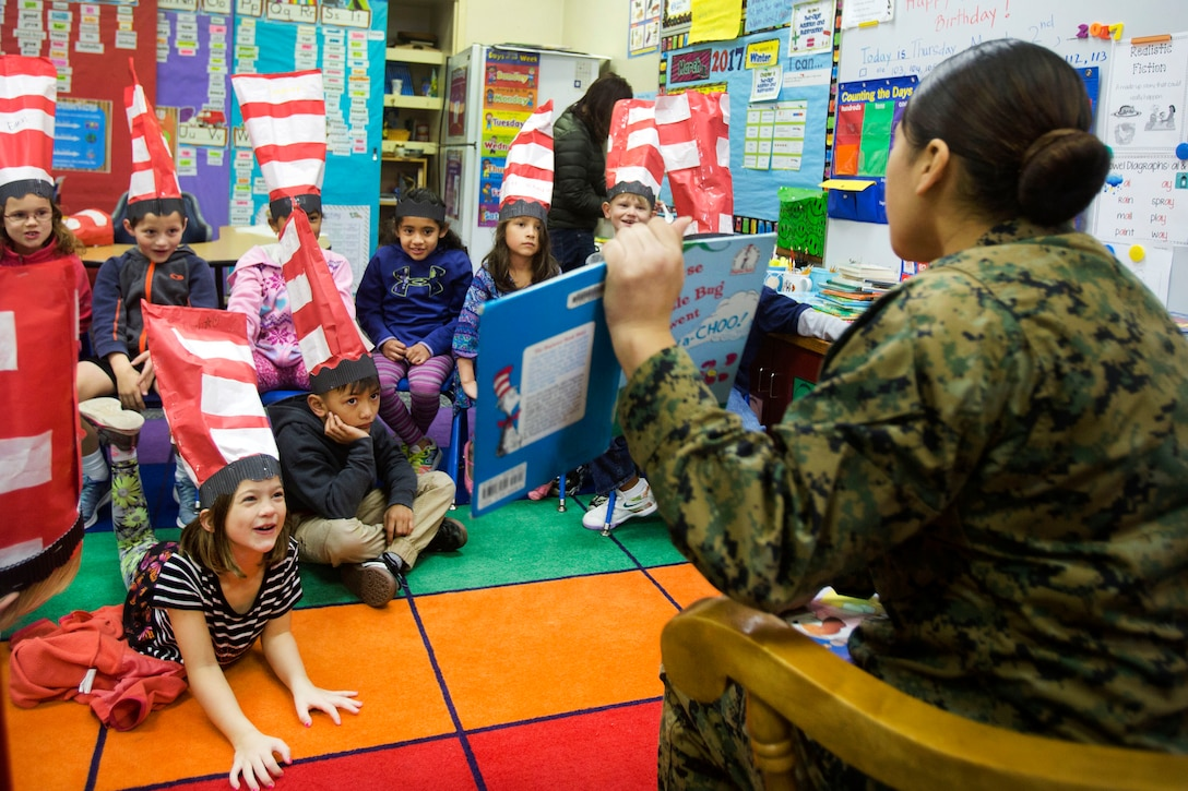 Marine Corps Lance Cpl. Saddie Martinez shows pictures from the book she's reading to students