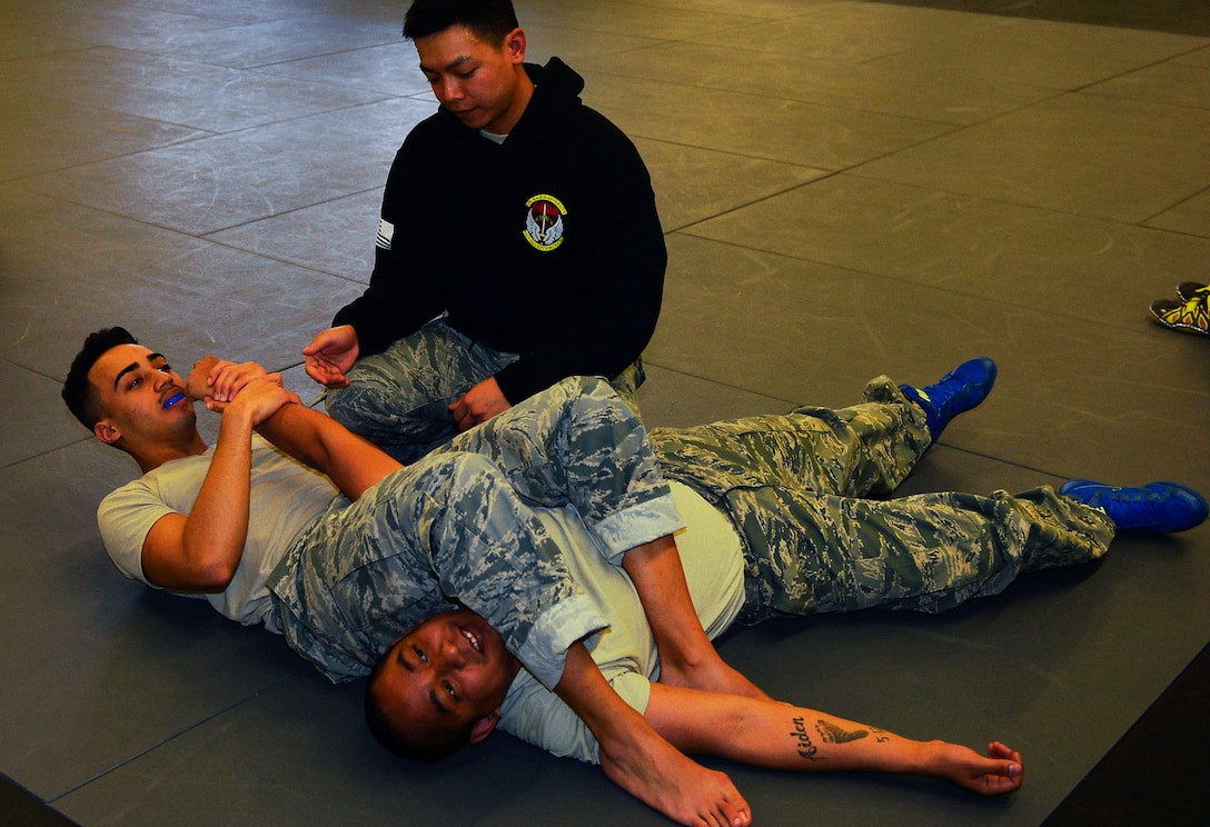 Staff Sgt. Jesse Sengsouk, 435th Security Forces Squadron ground combat readiness training center instructor, teaches security forces Airmen how to perform an arm bar submission during a combatives course on Ramstein Air Base, Germany, March 2, 2017. Instructors with the 435th SFS conduct the Fly Away Security Training program to prepare security forces Airmen, particularly from the 86gh SFS and 569th U.S. Forces Police Squadron, for scenarios they may face while on a mission. The 10-day course includes various submission techniques, baton training, and weapons disarmament. (U.S. Air Force photo by Airman 1st Class Joshua Magbanua)