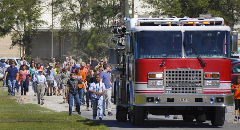 A fire truck leads the Operation Hero kid deployers to the 919th Special Operations Wing's annual Wing Day March 4 at Duke Field, Fla.  The Operation Hero event took place just prior to the Wing Day event.  The wing sets aside a special day each year to show appreciation for its reservists and their family members. Events included music, food, children's games, etc. (U.S. Air Force photo/Dan Neely)