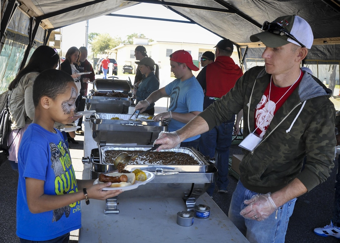 A volunteer serves up some beans to a 919th Special Operations Wing family member during the unit's annual Wing Day March 4 at Duke Field, Fla.  The wing sets aside a special day each year to show appreciation for its reservists and their family members. Events included music, food, children's games, etc. (U.S. Air Force photo/Dan Neely)