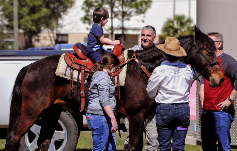 Col. James Phillips, the 919th Special Operations Wing commander, greets a family member during a pony ride at the unit's annual Wing Day March 4 at Duke Field, Fla.  The wing sets aside a special day each year to show appreciation for its reservists and their family members. Events included music, food, children's games, etc. (U.S. Air Force photo/Tech. Sgt. Kimberly Moore)