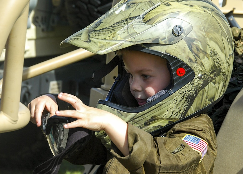 "A recent ""Operation Hero"" deployer dons a helmet while sitting in a security forces all-terrain vehicle during the 919th Special Operations Wing's annual Wing Day March 4 at Duke Field, Fla.  The wing sets aside a special day each year to show appreciation for its reservists and their family members. Events included music, food, children's games, etc. (U.S. Air Force photo/1st Lt. Monique Roux)"