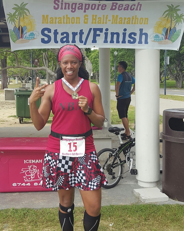 Enjoying a little bit of sunshine, Shalisa Davis stands in front of the start/finish in Singapore Beach, Singapore after finishing lucky number two.