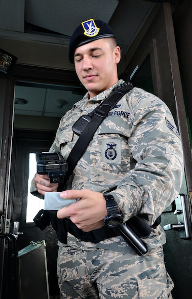 Senior Airman Blake Booth, with the 72nd Security Forces Squadron, uses the new Defense Biometrics Identification System while working at the Tinker Gate. (Air Force photo by Kelly White)