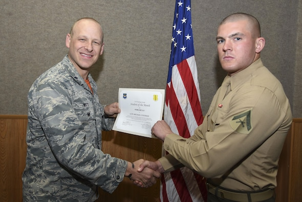 U.S. Air Force Lt. Col. Steven Watts, 17th Training Group Deputy Commander, presents the 316th Training Squadron Student of the Month award for Febuary 2017 to Lance Cpl. Michael Coleman, 316th TRS student, in the Brandenburg Hall on Goodfellow Air Force Base, Texas, March 3, 2017. (U.S. Air Force photo by Airman 1st Class Chase Sousa/Released)