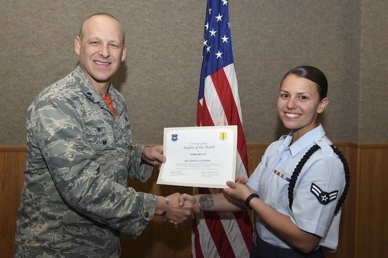 U.S. Air Force Lt. Col. Steven Watts, 17th Training Group deputy commander, presents the 315th Training Squadron Student of the Month award for Febuary 2017 to Airman 1st Class Jessica Cooper, 315th TRS student, in the Brandenburg Hall on Goodfellow Air Force Base, Texas, March 3, 2017. (U.S. Air Force photo by Airman 1st Class Chase Sousa/Released)