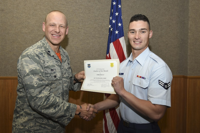 U.S. Air Force Lt. Col. Steven Watts, 17th Training Group deputy commander, presents the 312th Training Squadron Student of the Month award for Febuary 2017 to Airman 1st Class Nathaniel Fort, 312th TRS student, in the Brandenburg Hall on Goodfellow Air Force Base, Texas, March 3, 2017. (U.S. Air Force photo by Airman 1st Class Chase Sousa/Released)