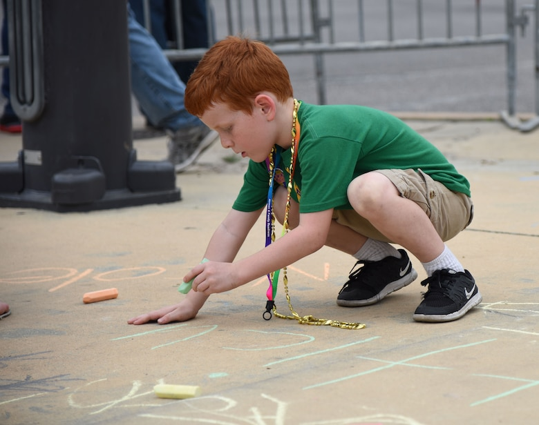 Atticus Fraites, son of Staff Sgt. Douglas Fraites, 85th Engineering Installation Squadron radio frequency transmissions team chief, draws on the side walk during the Gulf Coast Carnival Association Mardi Gras parade Feb. 28, 2017, in Biloxi, Miss. The 81st Force Support Squadron's Airman and Family Readiness Center staff invited families of deployed members to the event and provided food and entertainment to them prior to the start of the parade. (U.S. Air Force photo by Kemberly Groue)