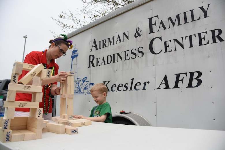 Alicia and Fox Cleary, family of Tech. Sgt. Richard Cleary, 336th Training Squadron instructor, play with building blocks during the Gulf Coast Carnival Association Mardi Gras parade Feb. 28, 2017, in Biloxi, Miss. The 81st Force Support Squadron's Airman and Family Readiness Center staff invited families of deployed members to the event and provided food and entertainment to them prior to the start of the parade. Alicia is a 336th TRS key spouse. (U.S. Air Force photo by Kemberly Groue)