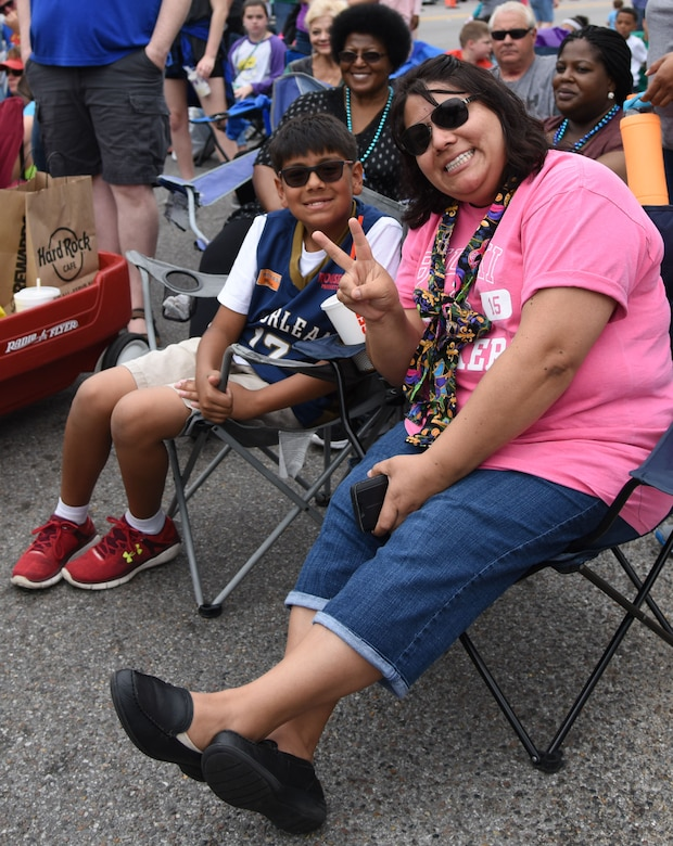 Veronica Hurtado, Keesler Child Development Center program assistant, and her son, Carlos, attend the Gulf Coast Carnival Association Mardi Gras parade Feb. 28, 2017, in Biloxi, Miss. Every Mardi Gras season, Keesler personnel participate in local parades to show their support of the communities surrounding the installation. The Keesler Honor Guard led the parade and members of base leadership also attended the event. (U.S. Air Force photo by Kemberly Groue)