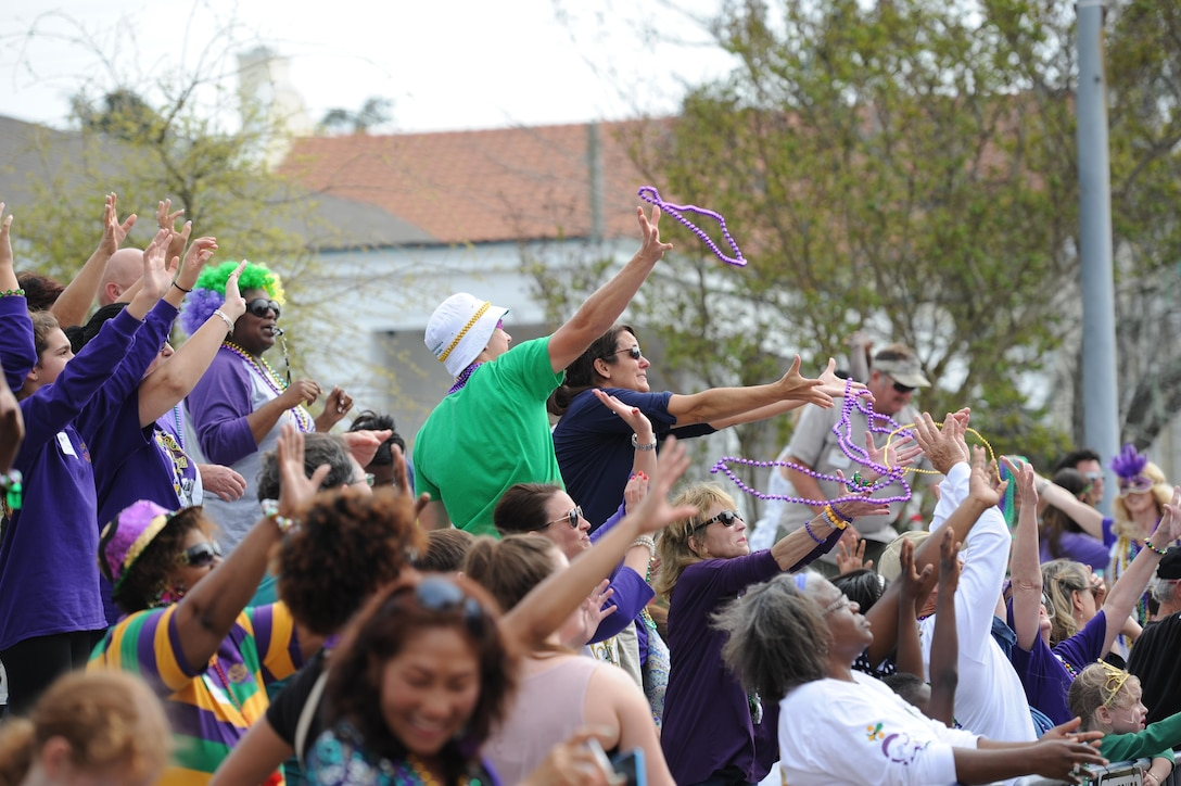Kristi and Mac Smith, family of Col. C. Mike Smith, 81st Training Wing vice commander, catch beads during the Gulf Coast Carnival Association Mardi Gras parade Feb. 28, 2017, in Biloxi, Miss. Every Mardi Gras season, Keesler personnel participate in local parades to show their support of the communities surrounding the installation. (U.S. Air Force photo by Kemberly Groue)
