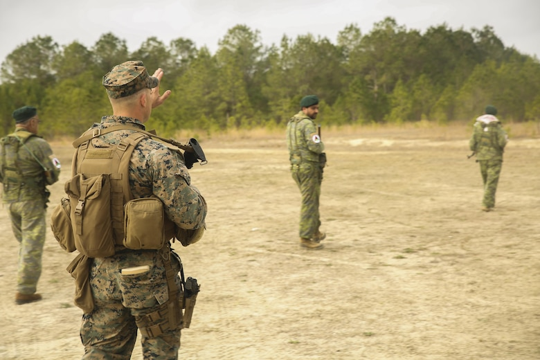 A Marine with Task Force Southwest instructs Afghan role players on proper patrolling techniques during a full mission rehearsal at Camp Lejeune, N.C., March 1, 2017. Throughout the week-long exercise, the Marines enhanced their advisory and combat skills in preparation for an upcoming deployment to Helmand Province, Afghanistan. Task Force Southwest is comprised of approximately 300 Marines who will train, advise and assist the Afghan National Army 215th Corps and 505th Zone National Police. (U.S. Marine Corps photo by Sgt. Lucas Hopkins)